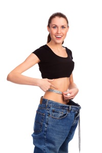 Girl demonstrating weight loss by wearing an old pair of jeans. Isolated on white background