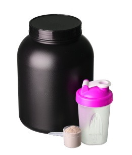 big tub of whey protein with pink shaker and cup of protein powd