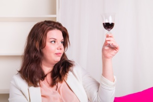 Plump and young woman tests a glass of red wine