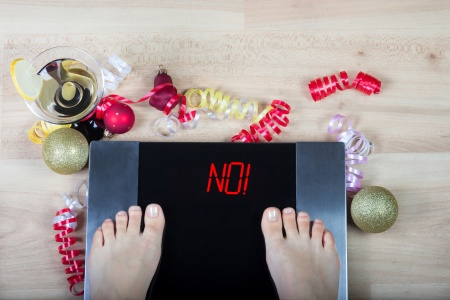 "Digital scales with female feet on them and sign""no!"" surrounded by Christmas decorations and glass of vermouth. Shows how alcohol and unhealthy lifestyle during xmas holidays effect our body."