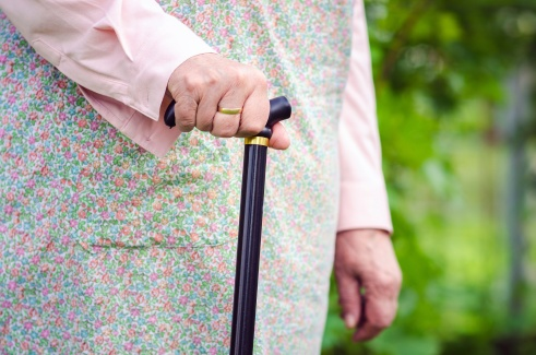 Old obese woman walking with stick